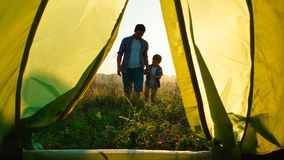 Father with son walks to a tent. View from the tent at the sunset Royalty Free Stock Photo