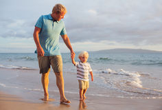 Father and son wallking on the beach Stock Photo
