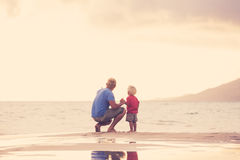 Father and son wallking on the beach Stock Images