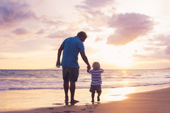 Father and son wallking on the beach Royalty Free Stock Photo