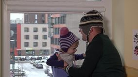Father with son in warm hats have fun near window. Family prepare to go outside stock video