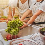 Father with son washes vegetables Royalty Free Stock Photo