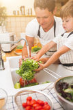 Father with son washes vegetables before eating Royalty Free Stock Photo