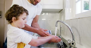 Father and son washing hands in the kitchen sink