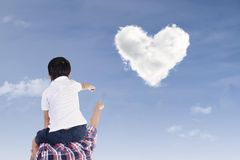 Father and son watch heart clouds. Father and son are pointing at heart shape clouds under blue sky Stock Image