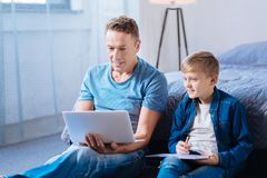 Father and son watching educational video together Stock Images