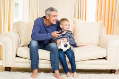 Father and son watching football match on tv. Sitting on the sofa Royalty Free Stock Image