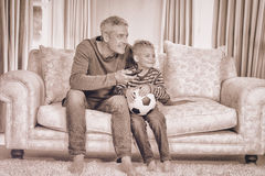 Father and son watching football match on tv. Sitting on the sofa Royalty Free Stock Photos