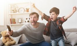 Father and son watching football on TV at home. Emotional father and son watching football on TV and cheering favorite team at home royalty free stock image