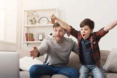 Father and son watching football on TV at home. Emotional men and little boy cheering their favorite team, family enthusiasm, copy space Royalty Free Stock Image