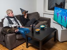 Father and son watching football world cup soccer on tv. German father and son watching football world cup soccer on tv together on sofa at home. They are Stock Photography