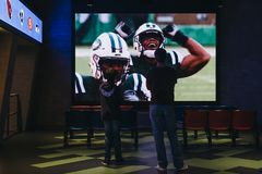 Father and son watching a game in NFL Experience in Times Square, New York, USA. Father and son watching a game in NFL Experience in Times Square, New York, a royalty free stock images