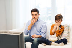 Father and son watching horror movie on tv at home. Family, people, technology, television and entertainment concept - scared father and son watching horror Stock Photo