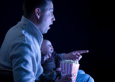 Father and son watching a movie. Caucasian   father and son watching a movie on tv and eating popcorn Stock Photos