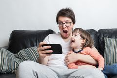 Father and son watching a scary video on the phone sitting on a sofa on a white background. They`re screaming. A little boy and. His dad have fun at home royalty free stock photo