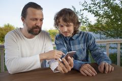 Father and son watching the smartphone garden on the terrace on stock image