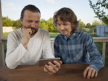 Father and son watching the smartphone garden on the terrace on. A summer day, family Royalty Free Stock Photography