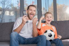 Father and son watching soccer match Royalty Free Stock Image