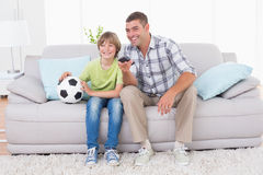 Father and son watching soccer match on sofa royalty free stock images