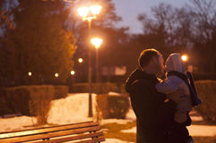 Father and son watching the street lamps at night, winter landscape. Father and his son watching the street lamps at night, winter landscape Royalty Free Stock Photography
