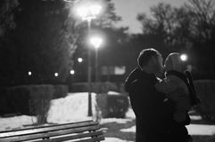 Father and son watching the street lamps at night, winter landscape. Black and white photography Stock Image