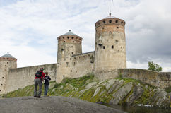 Father and son watching and taking a picture of olavinlinna castle Stock Images