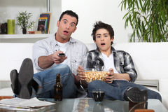Father and son watching television Stock Images
