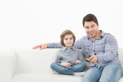 Father and son watching television together on the couch Royalty Free Stock Photo