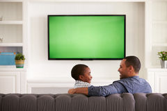 Father and son watching TV looking at each other, back view stock photo