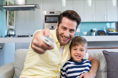 Father and son watching tv together on the couch Royalty Free Stock Photos