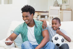Father and son watching tv together on the couch Royalty Free Stock Photography