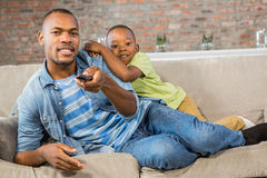 Father and son watching tv together on the couch Stock Image