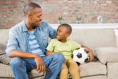 Father and son watching tv together on the couch Stock Photos