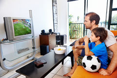 Father and son watching tv together. Father and son watching football world cup soccer on tv together in living room on sofa being excited fans royalty free stock photos
