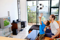 Father and son watching tv together. Father and son watching football world cup soccer on tv together in living room on sofa being excited fans stock photos