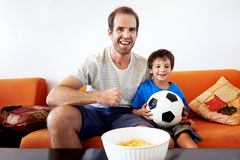 Father and son watching tv together. Father and son watching football world cup soccer on tv together in living room on sofa being excited fans stock photography