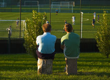 Father And Son Watching Younger One's Game. Father and elder son watching younger one's soccer game Royalty Free Stock Images