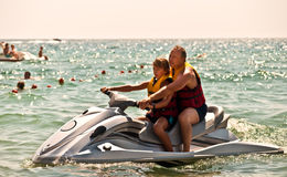 Father and son on a water bike . Happy family on the water in the sea Royalty Free Stock Photo