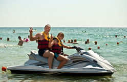 Father and son on a water bike . Happy family on the water in the sea Royalty Free Stock Photography