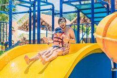 Father and son on a water slide in the water park Stock Photos