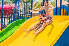 Father and son on a water slide in the water park Stock Photography