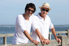 Father and son by waterfront Royalty Free Stock Image