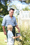 Father and son watering plants. In garden Royalty Free Stock Photos