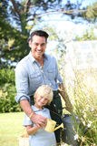 Father and son watering plants. In garden Stock Photo