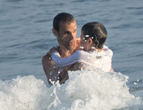 Father and son in a wave in the ocean Royalty Free Stock Photography