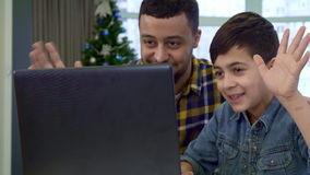 Father and son waving at the laptop stock video