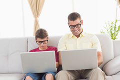 Father and son wearing novelty glasses while using laptop. Happy father and son wearing novelty glasses while using laptop on sofa at home Royalty Free Stock Photos