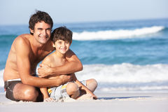 Father And Son Wearing Swimwear Sitting Down Stock Photography