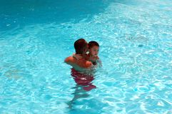 Father and Son wim in pool. A father and son swim in a pool together Royalty Free Stock Photos
