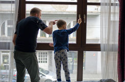 Father and son at window Royalty Free Stock Image
